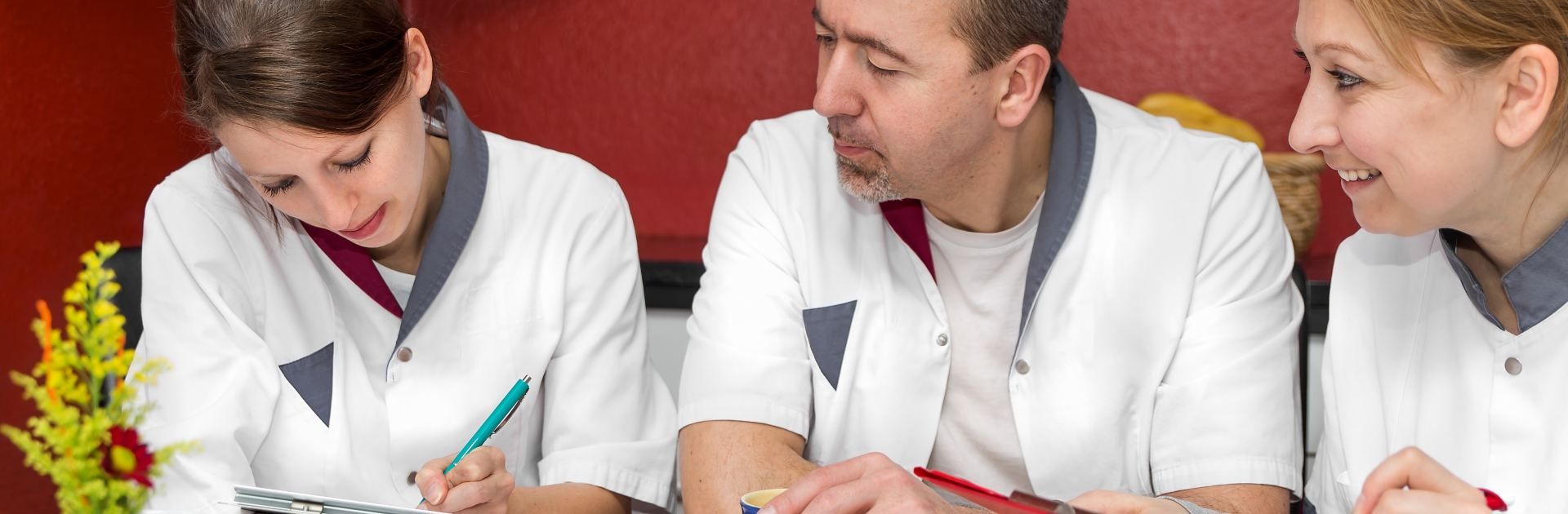 Drei Pfleger notieren sich Daten im Besprechungsraum